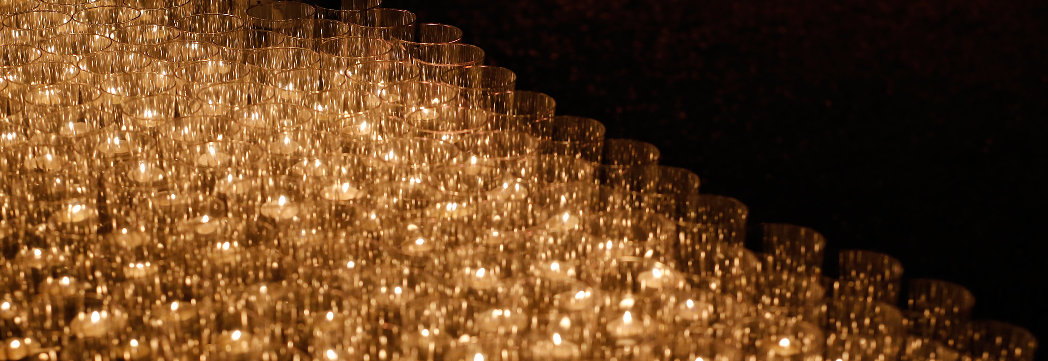 Rows of lit candles on dark background from Take Back the Night event
