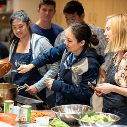 ARC chef Jessica VanRoo does cooking demonstration, dumping food from a pan into a pot while students watch