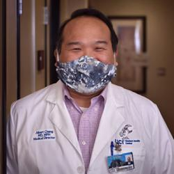 Student Health Center medical director Dr. Albert Chang in lab coat wearing fabric face covering