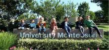 Children sitting on a University Montessori sign